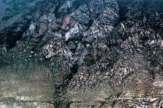 西藏特有的巨石构成的巍峨山体下,镶嵌在绿树丛中一片片金色的青稞地