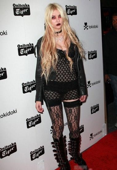 被称为垃圾摇滚的代表泰勒 摩森黑色镂空上衣搭配黑色蕾丝legging,造型感十足的长靴极具个性。