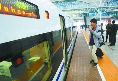 图为昨日上午7时12分,乘客走向即将出发的第一列由武汉开往深圳的动车组列车。记者 金思柳 摄