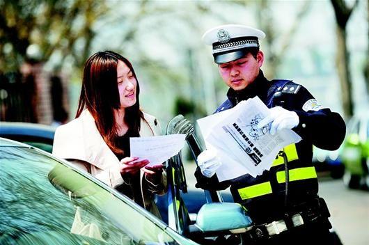 昨日,武汉东湖交警项坤为外地自驾来汉的游客发放停车及导游地图。(记者田悦 实习生蒋亚霖 冯骋摄)