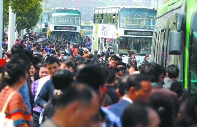 昨日,在扁担山墓园门前的公汽车站,大量市民在排队等候返程的公汽.