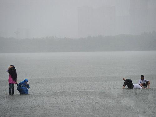 6月23日下午18时29分,武汉大学4名留学生在湖中浴雨