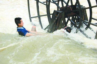 图为当地导游正奋力营救因救人而卡入水车的郭先生