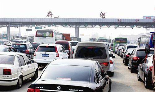 图为:一到节假日,高速公路收费站前总会排起车辆长龙 记者魏铼摄