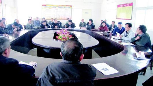 楚天都市报讯 图为:何永存(右二)在主持召开村民代表大会