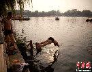 北京持续晴热高温 市民湖里游泳避暑