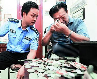 图为:专家协助民警对这些古钱币进行鉴定 图片来自楚天都市报 记者佟建国摄