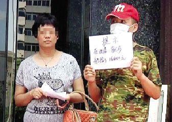齐先生和王女士在餐馆门口举着白板。本报记者 吴边 摄