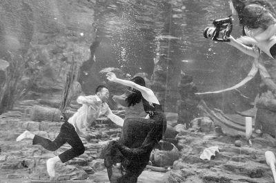 摄影师在水中给新人拍摄婚纱照。