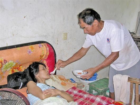 楚天都市报讯 图为:王有茂老人给瘫痪的儿媳冯群桃喂水