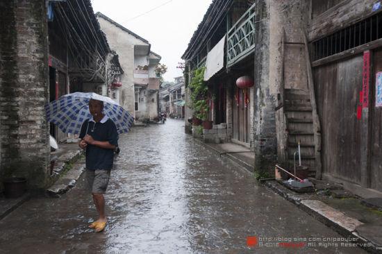 撑伞走过的古镇居民