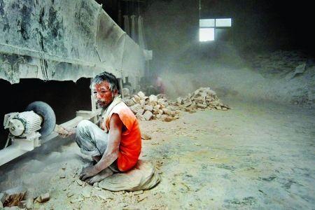 工人身上落满粉尘。图片来源:大河报