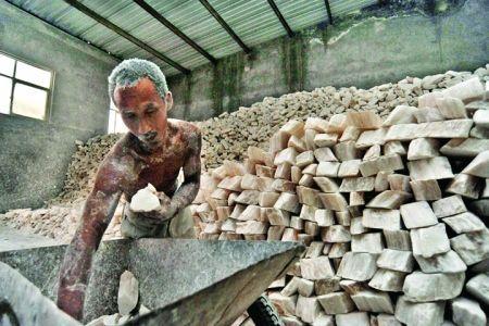 工人赤膊将石膏一块块搬下车,码放整齐。