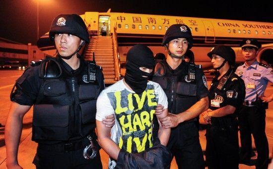 9月2日凌晨,在湖北省武汉市,犯罪嫌疑人熊毅(中)被警方从飞机上押解下来。新华社记者 程敏 摄