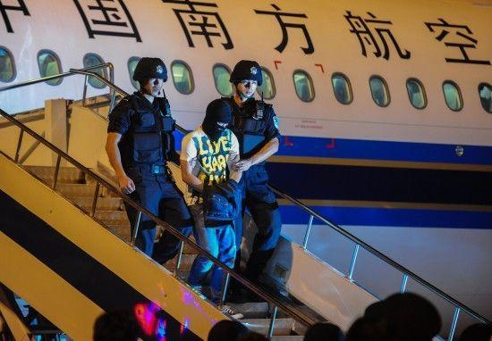 9月2日凌晨,在湖北省武汉市,犯罪嫌疑人熊毅(中)被警方从飞机上押解下来。新华社记者程敏摄