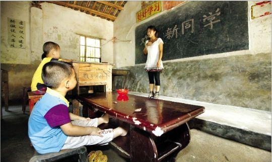 9月1日,麻城市顺河镇长冲村村小教室内,课桌大小各不相同,一名学生家长将茶几搬来给孩子当课桌。本报记者 王筝 摄