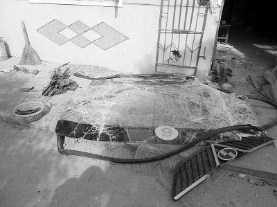 6路公交车的挡风玻璃被撞碎在民房前。 见习记者谭德磊 摄