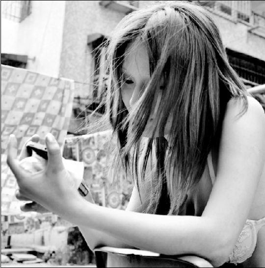 昨日,在青山建设七路,于青青(化名)正在用记者的手机查看网上关于她的照片。本报记者 傅坚 摄
