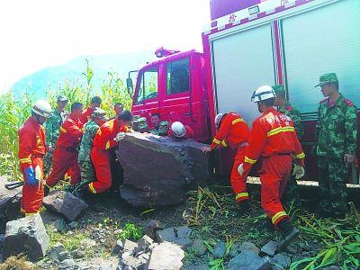 在震中洛泽河镇,救援官兵移开阻挡道路的落石。