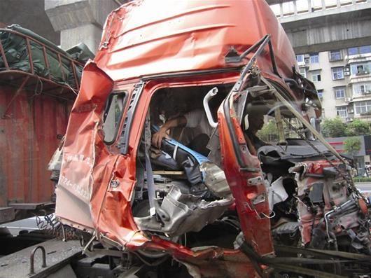 货车车头破损司机蜷缩与公交车街头并行