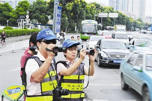 """图为:昨日,武汉""""拔塞行动""""志愿者正式上岗。志愿者在汉口建设大道新华路口监督拍摄违法加塞车辆。 记者魏铼摄"""