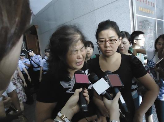 图为:宣判后情绪悲痛的肖桂莲在大女儿陪伴下走出法庭