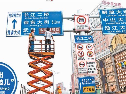 昨天下午,在长江大桥汉口黄浦大街上桥处,两名工作人员正在更新路牌
