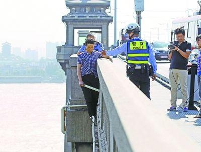 图为欲轻生妇女站在大桥护栏外。记者杨涛 摄