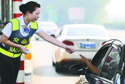 昨天上午,武黄高速武东收费站,收费人员站在收费亭外发放通行卡,加速放行车辆。记者王翮 摄