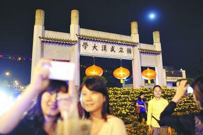 昨晚20时左右,武汉大学正门口,几名学子正在牌坊下拍照留念。 记者 周超 摄