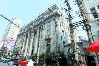 """扬子街上的建设银行老楼被9根电线杆""""包围""""。 记者李子云 摄"""