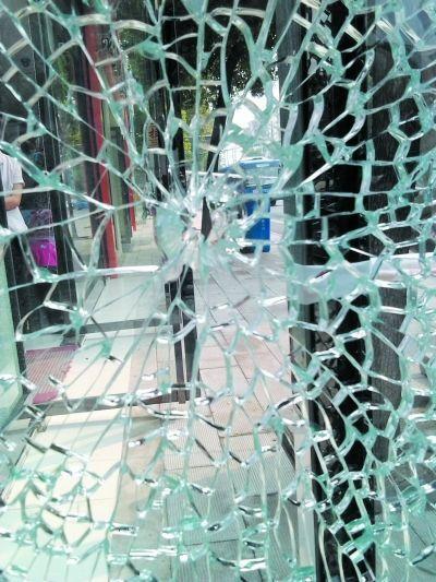图为一家家纺店的大门和橱窗玻璃均被击裂。记者史强 摄