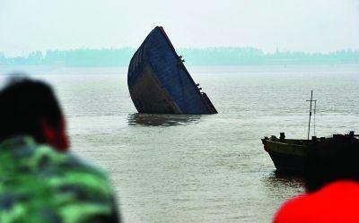 船尾部分沉入江中,船头部分露出江面。记者李子云 摄