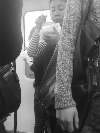 两名女子站在轻轨车厢里过早。 记者李少文 摄