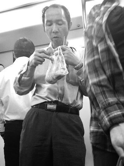 在轻轨车厢里,一名男子靠着立柱吃煎包。记者李少文 摄