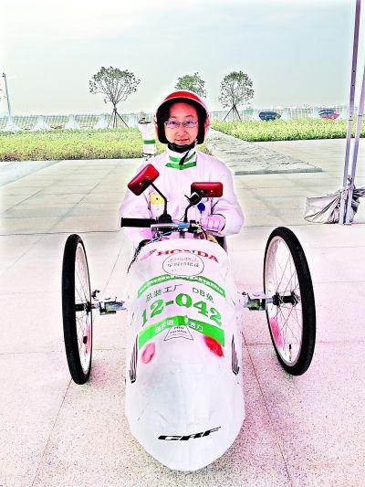张琼坐在自制节能车内准备出发。记者 冯欣楠 摄