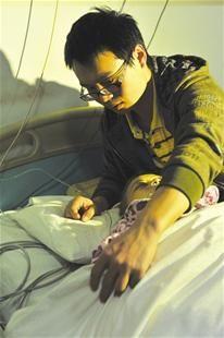 图为:前日,程威为母亲小心盖好被单
