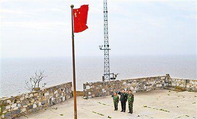 仰望着高高飘扬的五星红旗,记者和老王夫妇都不由自主地举手致以庄严的军礼……(见图)。田亚威摄