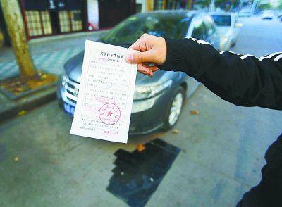左图:停车线已被沥青覆盖,车主领到罚单。记者杨涛 摄