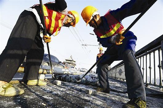 工人在铲除长江大桥上的旧人行道橡胶垫 记者程铭摄