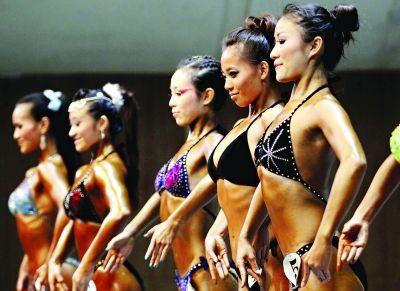 全国健身大赛在汉举行。图为参加2012年中国健身公开赛系列赛总决赛的健美小姐在昨日的比赛中 记者 李葳 摄
