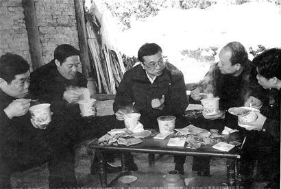 图为:2008年1月31日,李克强在川北山区察看雪灾灾情,期间与陪同人员一起边吃方便面边研究救灾工作。