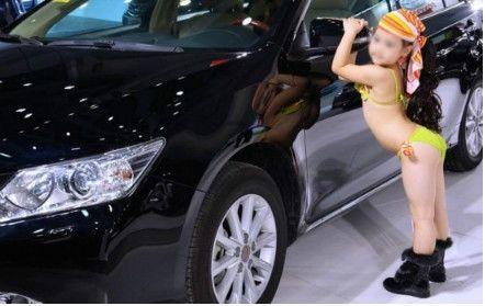 图为汽车文化节上和成年模特一起亮相的童模。