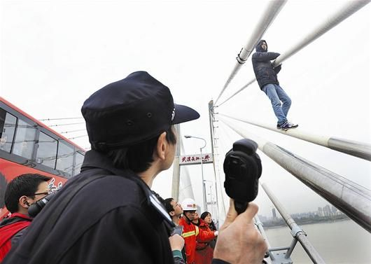 众人劝说下,男子慢慢爬下大桥