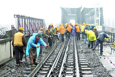 昨日,铁路工人们冒严寒、顶风雨维修汉水铁路桥 记者 陈卓 摄