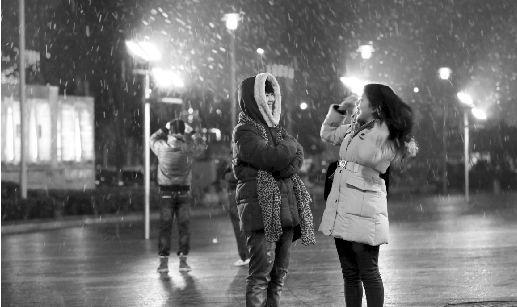 昨日,菱角湖万达广场,突降大雪,两女孩在欣赏飘落的雪花。本报记者 傅坚 摄