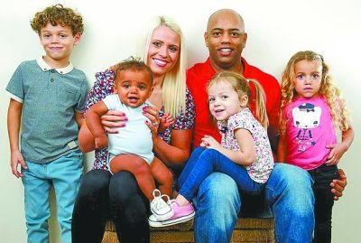 """吉丁斯夫妇和他们的4个儿女:前排第3个就是""""白人""""女儿艾米娅。"""