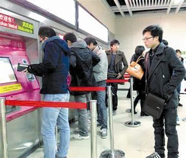 楚天都市报讯 图为:昨晚6时许,地铁2号线洪山广场站内,乘客在自动售票机上购票