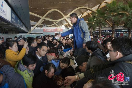 2013年1月4日,昆明,滞留的旅客和新增旅客让候机大厅一片嘈杂。一名不能办理登机手续的旅客情绪激动,跳上值机柜台。图片来源:cfp