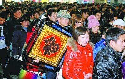 """在武昌火车站,一位农民工朋友手里拿着""""福""""字排队乘车。记者金思柳 摄"""